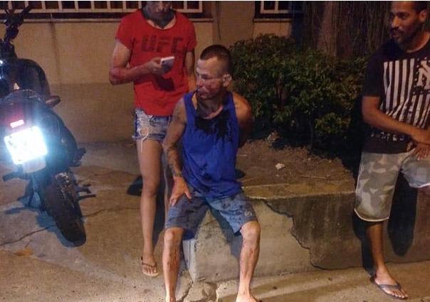 강도가 망연자실한 표정으로 경찰을 기다리고 있다. 뒤에 휴대폰을 하고 있는 사람이 비아나 - 트위터 갈무리