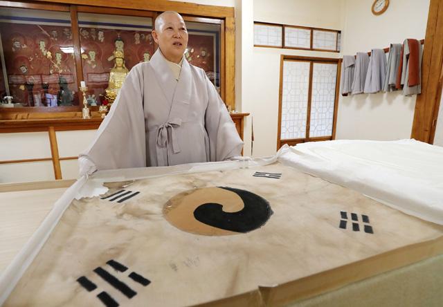 '진관사 태극기' 영인본을 살펴보며 2009년 발견 당시 상황을 전하는 진관사 주지 계호 스님.