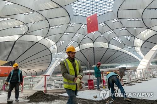 지난 20일 베이징 다싱공항 건설현장에서 노동자들이 작업하고 있다. [로이터=연합뉴스]