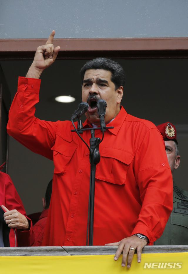 """【카라카스=AP/뉴시스】니콜라스 마두로 베네수엘라 대통령이 23일(현지시간) 수도 카라카스 미라플로렌스 대통령궁밖에 모인 지지자들을 향해 연설하고 있다. 마두로 대통령은 """"베네수엘라가 미국과의 정치·외교 관계를 단절한다""""고 선언했다. 2019.01.24"""