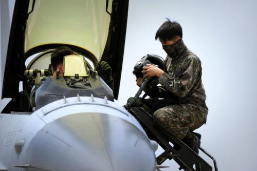 공군 정비사가 KF-16 조종석에 탑승한 조종사로부터 헬멧을 넘겨받고 있다. 미 공군 제공