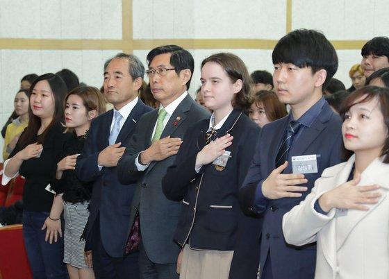 박상기 법무부 장관(가운데)이 지난달 21일 서울 용산구 국립한글박물관 대강당에서 열린 제1회 대한민국 국적증서 수여식에서 국기에 대한 경례를 하고 있다. [법무부 제공]