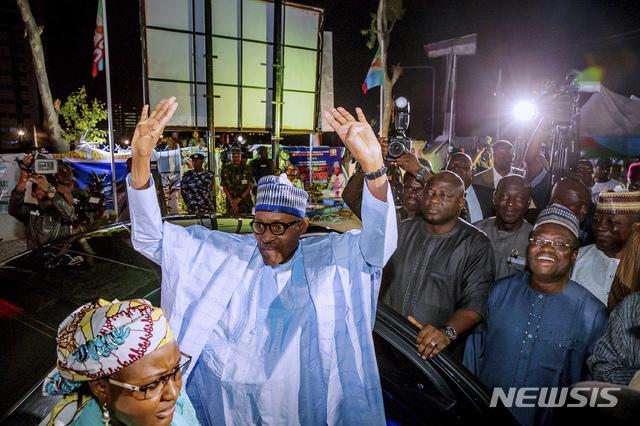 【아부자(나이지리아)=AP/뉴시스】나이지리아 대선에서 차기 대통령으로 확정, 재선에 성공한 무하마두 부하리 현 나이지리아 대통령이 27일(현지시간) 수도 아부자에서 여당인 범진보의회당(APC) 당원들과 지지자들에게 수락 연설을 하기 전 손들어 인사하고 있다. 부하리 대통령은 지난 23일의 선거에 앞서 대대적인 선거운동을 벌이면서 만연한 부패, 안보, 경제난과 싸울 수 있도록 다시 한번 기회를 달라고 유권자들에게 호소했다. 2019.02.27.