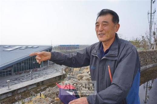강동균 강정마을 해군기지반대주민회장이 지난 4일 제주 서귀포시 강정동에서 서울신문과 만나 해군기지를 바라보며 해군기지 완공 전 마을의 모습을 설명하고 있다. 뒤로 보이는 건물은 민군복합크루즈터미널이다.