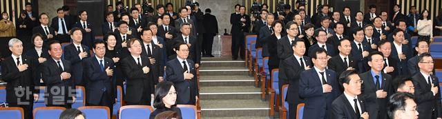 자유한국당 의원들이 15일 국회에서 열린 의원총회에 '의회 민주주의 사망'을 주장하며 검정색 옷과 넥타이를 착용하고 참석해 국민의례를 하고 있다. 오대근기자