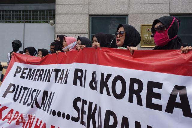 [저작권 한국일보]㈜에스카베(SKB) 노동자들이 '인도네시아와 한국 정부는 언제 내 월급을 돌려줄 것인가'라는 문구를 들고 14일 주인도네시아한국대사관 앞에서 집회하는 모습. 자카르타=고찬유 특파원