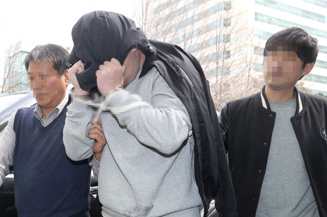'청담동 주식 부자' 이희진 씨 부모 살해 용의자 김모(34) 씨가 18일 오전 경기 안양시 동안경찰서에서 조사를 받기 위해 이동하고 있다. 경찰은 나머지 용의자 3명을 쫓고 있다. 연합뉴스