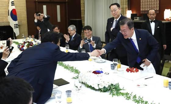 문재인 대통령(오른쪽)이 지난해 5월 9일 일본 도쿄 총리공관에서 열린 한일 정상회담 오찬에서 아베 신조 일본 총리로부터 대통령 취임 1주년 기념 축하 케이크를 받은 뒤 총리와 악수하고 있다.청와대사진기자단