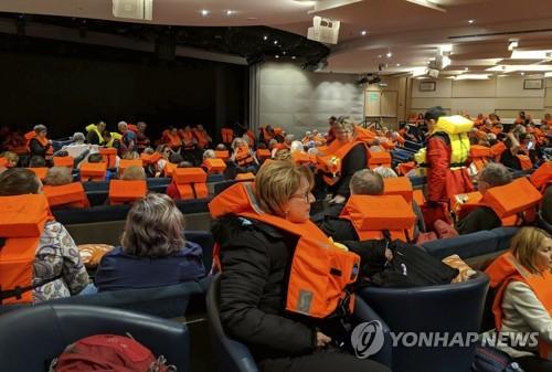 크루즈선에서 구명조끼를 입은 채 대기 중인 승객들 [AP=연합뉴스]