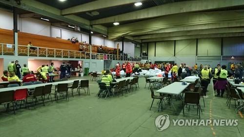 실내체육관의 구조대원과 자원봉사자들 [로이터=연합뉴스]