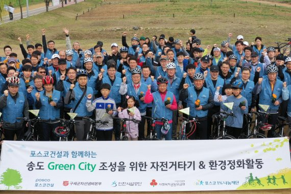 포스코건설 봉사단이 지난 20일 인천 송도 달빛공원과 해돋이공원에서 자전거를 타면서 꽃밭을 가꾸는 행사에 참여해 포즈를 취하고 있다.