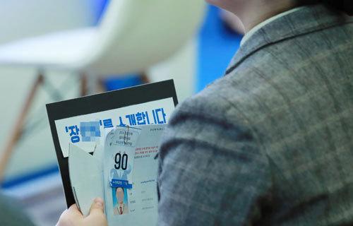 취업준비생이 특별히 준비한 자기소개 패널을 손에 든채 한 은행의 현장 면접을 기다리고 있다.