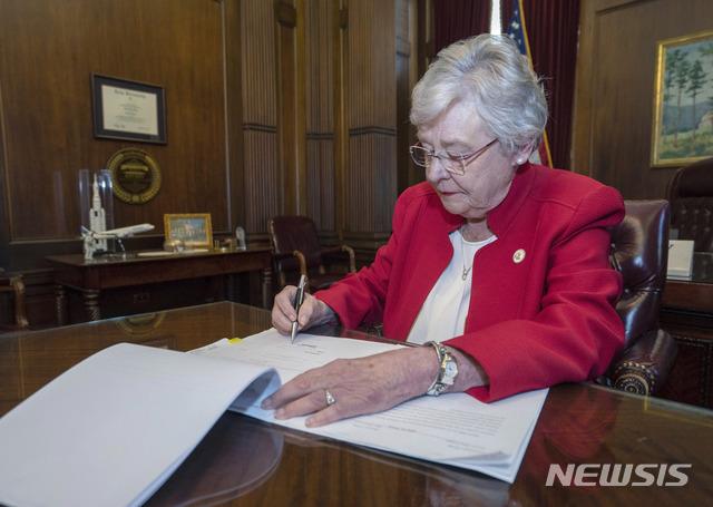 【몽고메리(미 앨라배마주)=AP/뉴시스】케이 아이비 미 앨라배마 주지사가 15일(현지시간) 몽고메리에서 임산부의 생명이 위험한 경우를 제외한 모든 낙태를 중범죄로 규정해 금지하는 낙태금지법안에 서명하고 있다. 2019.5.16