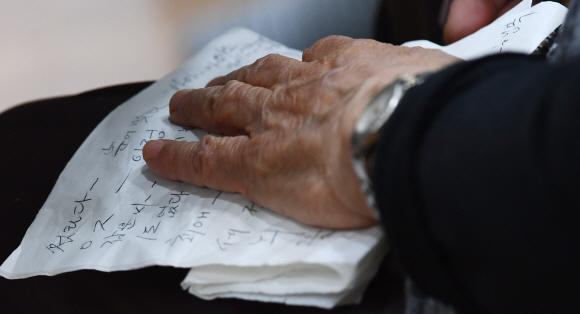 따뜻하게… - 노인 소외 해결 프로그램 '너와 나의 연결고리' 신조어 퀴즈에 참가한 한 어르신이 잘 맞히고 싶어서 준비해 둔 메모를 보며 퀴즈를 풀고 있다.