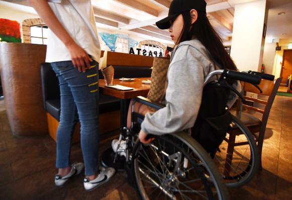 - 서울 혜화역 인근에서 SUNNY들이 장애인 문화시설 지도를 제작하기 위해 한 음식점을 찾아 휠체어를 타고 테이블 높이를 측정하고 있다.