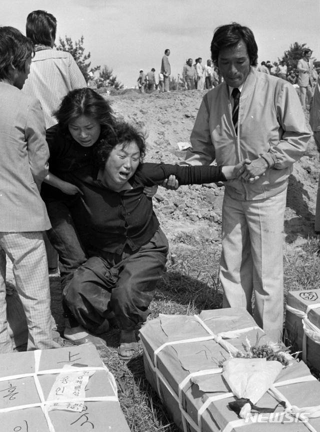 【광주=뉴시스】변재훈 기자 = 18일 오전 5·18민주화운동 39주년 기념식이 열린 가운데 문재인 대통령이 1980년 5월21일 광주 금남로에서 계엄군의 총에 맞아 숨진 김완봉 군(당시 15세)의 묘를 찾아 참배했다. 사진은 당시 김 군의 어머니가 아들의 관 앞에서 오열하고 있는 모습. 2019.05.18. (사진=5·18기념재단 제공)photo@newsis.com