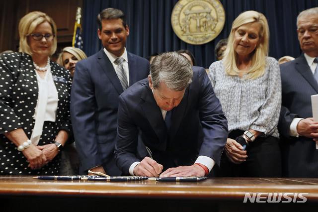 【애틀랜타=AP/뉴시스】공화당 소속 브라이언 켐프 조지아주지사가 지난 7일 조지아 주도 애틀랜타에서 배아 심박감지 시점부터 낙태(임신중단) 시술을 금지하도록 한 새 주법에 서명하고 있다. 그는 이후 지난 18일 새 법을 비판하고 나선 스타들을 향해 'C급'이라고 비난했다. 2019.05.20.