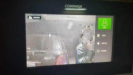 21일 오전 대구 북구 태전동 한 빌라 건물 앞에서 대구 강북경찰서 한 지구대 소속 A 경위가 민원인 B씨 집 앞에서 담배를 피우며 벨을 누르고 있는 모습이 인터폰 화면에 찍혀 있다. [사진 독자]