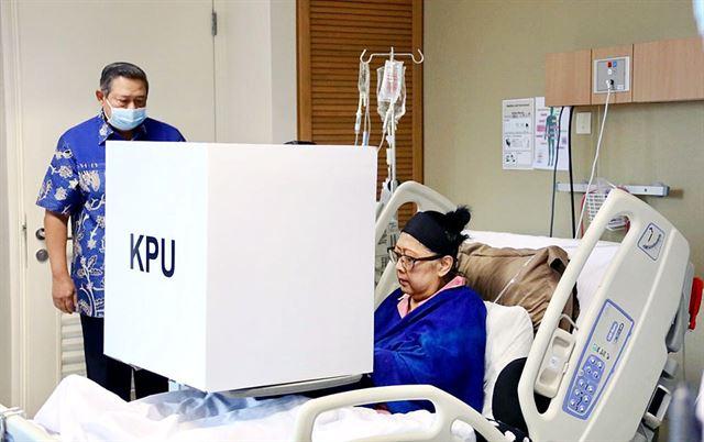 아니 유도요노 여사가 지난 4월 싱가포르 국립대병원에서 투병 중임에도 인도네시아 대선 재외국민투표에 참여해 한 표를 행사하고 있는 모습. 그 곁에 평생의 반려 수실로 밤방 유도요노 전 대통령이 서 있다. 인터넷 캡처