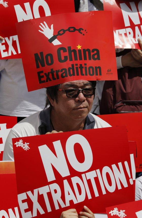 지난 9일(현지시간) 홍콩에서 벌어진 '범죄인 인도 법안' 반대 시위에서 한 남성이 '중국으로의 송환을 반대한다'는 팻말을 높이 들고 있다. [AP=연합뉴스]