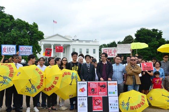 지난 9일(현지시간) 미 워싱턴 백악관 앞에서 홍콩인들이 모여 노란우산을 들고 '범죄인 인도 법안' 반대 시위를 열고 있다. [트위터 캡처]