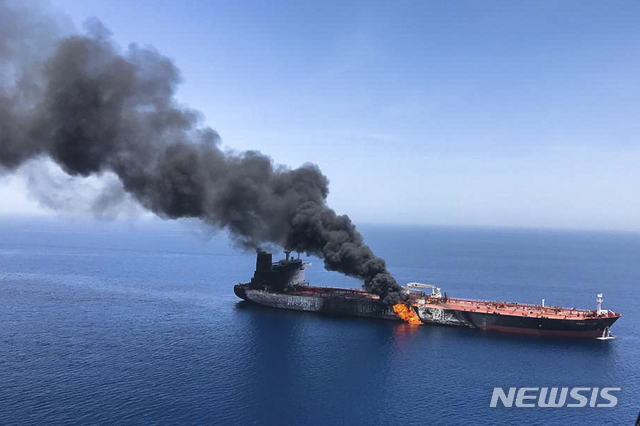 【오만만=AP/뉴시스】이란의 ISNA 통신이 제공한 사진으로, 13일 이란 앞 호르무즈 해협에서 오만만으로 내려가는 바다에서 유조선 한 척에 불이 붙어 검은 연기가 솟아오르고 있다. 이날 이 해역에서 두 척의 유조선이 폭발음을 동반한 공격을 받아 선원들이 배를 버렸다. 두 배의 선원 44명 전원은 이란 구조선에 옮겨 탔다. 2019. 6. 13.