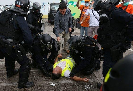홍콩 경찰들이 쓰러진 시민을 지켜보고 있다. 홍콩의 자유와 인권도 이렇게 쓰러지는 게 아닌가 하는 우려가 커지고 있는 게 홍콩의 현실이다. [로이터=연합뉴스]