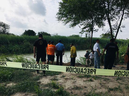미국과 접경지인 멕시코 마타모로스 강가에서 경찰과 주민들이 24일(현지시간) 2세 여아와 20대 아빠가 미국으로 가기위해 강물을 건너려다 시신으로 발견된 지점을 바라보고 있다. AP뉴시스