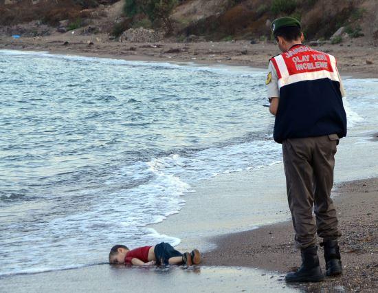 2015년 9월2일(현지시간) 터키 남서부 물라주 보드룸의 해안에서 시리아 북부 코바니 출신 에이란 쿠르디(3)의 시신을 터키 현지 경찰이 수습하기 전 현장을 조사하고 있다. 쿠르디는 보드룸을 떠나 그리스 코스섬으로 향하던 중 에게해에서 배가 침몰해 익사했다. AP뉴시스