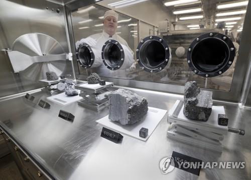 질소를 채운 용기에 전시된 달 샘플 원형 부분은 손을 넣어 달 샘플을 처리할 수 있는 고정장갑. [AP=연합뉴스]