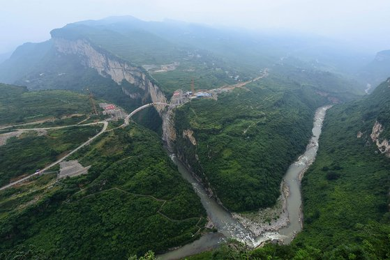 중국 남서부 쓰촨(四川)성, 구이저우(九州), 윈난(雲南)성 접경지역에 위치한 아치교가 협곡 위에 7일(현지시간) 연결됐다. 아치교 위에 올려질 주 대교는 올 연말 완공될 예정이다. [AFP=연합뉴스]