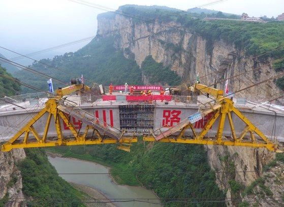 ( 중국 남서부 쓰촨(四川)성, 구이저우(九州), 윈난(雲南)성 접경지역에 위치한 아치교가 협곡 위에 7일(현지시간) 연결됐다. 아치교 위에 올려질 주 대교는 올 연말 완공될 예정이다. [신화=연합뉴스]
