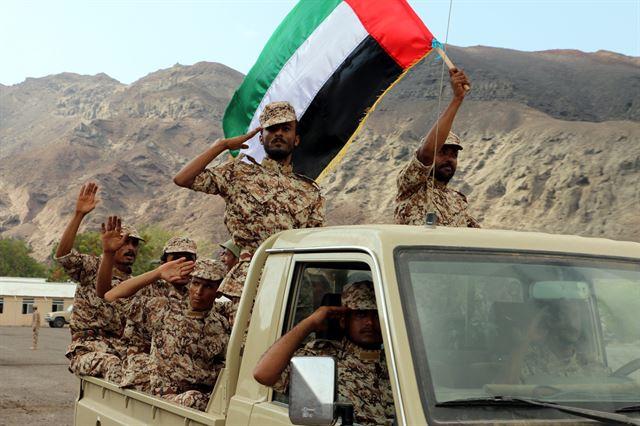 2017년 9월 29일 예멘 남부 항구도시에서 열린 전투 훈련 중 아랍에미리트(UAE) 육군 병사들이 군용 트럭에 올라 UAE 국기를 흔들면서 경례를 하며 지나가고 있다. 이들은 예멘 현지에서 신병 훈련을 받은 군인들이다. UAE는 2015년 3월 이후 사우디아라비아 주도의 아랍동맹군으로서 예멘 전쟁에 깊숙이 개입, 후티반군과 싸우는 예멘 정부군을 지원해 왔으나 지난 8일 '전략적 재배치' 차원에서 자국 군대를 일부 철수할 방침이라고 밝혔다. EPA 연합뉴스