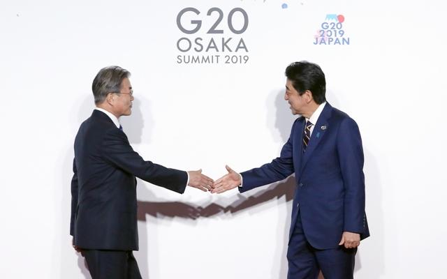 문재인 대통령이 6월28일 오전 주요 20개국(G20) 정상회의 공식환영식에서 일본 아베 신조 총리와 악수하고 있다. 연합뉴스