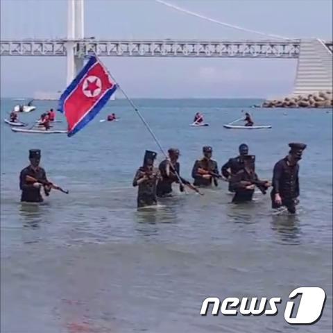 24일 오후 2시쯤 부산 수영구 광안리해수욕장에서 전국대학생대표자협의회 소속 8명이 북한군인 옷차림을 하고 모의총기를 든 채 퍼포먼스를 하고 있다. 이같은 장면은 유튜브를 통해 실시간 중계됐다.(SNS 캡처)© 뉴스1