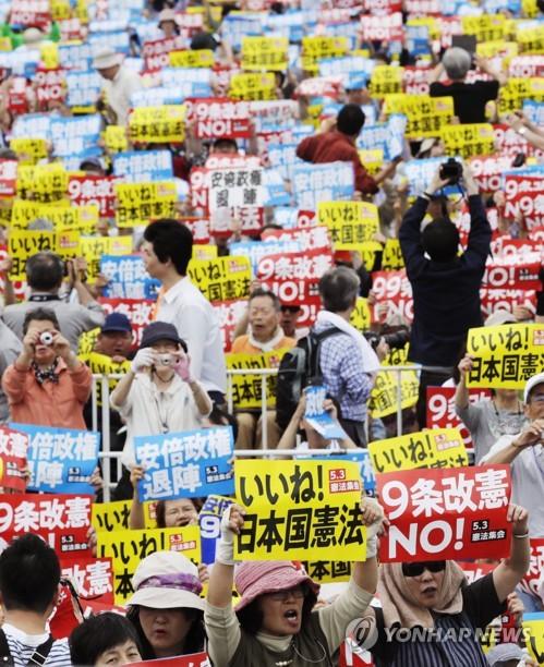 작년 5월 일본 도쿄(東京) 고토(江東)구에서 열린 개헌반대·아베 신조(安倍晋三) 총리 퇴진 촉구 집회에서 참가자들이 플래카드를 든 채 구호를 외치는 모습 [교도=연합뉴스 자료사진]