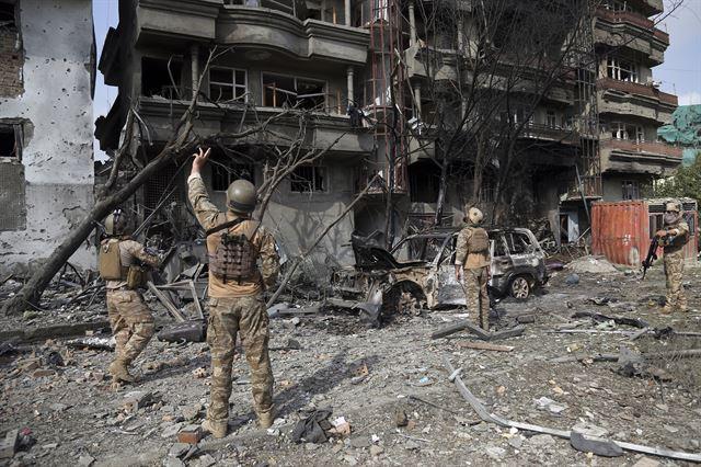 지난달 29일 아프가니스탄 수도 카불에서 보안군 병사들이 전날 차량폭탄 테러 공격 현장을 조사하고 있다. 오는 9월 28일 대선에 부통령 후보로 나서는 암룰라 살레 전 아프간 국가안보국(NDS) 국장이 이끄는 정당 '아프간 그린 트렌드(AGT)'의 사무실이 있는 건물로, 살레 전 국장에 대한 암살 시도로 해석되고 있다. 살레 전 국장은 긴급대피해 목숨을 건졌지만, 이 공격으로 최소 20명이 숨졌다. 카불=AP 연합뉴스