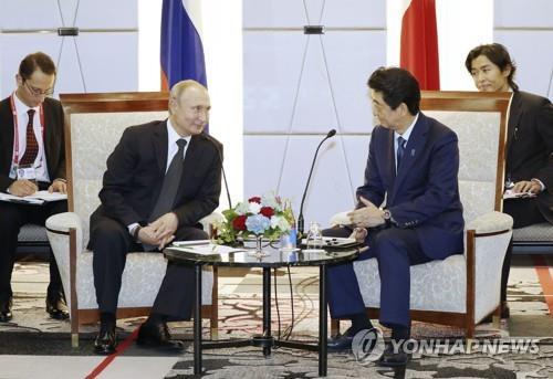 지난 6월 29일 오사카에서 열린 주요 20개국(G20) 정상회의 때 블라디미르 푸틴 러시아 대통령(왼쪽)이 아베 신조 총리를 만나 회담하고 있다. [교도=연합뉴스 자료사진]