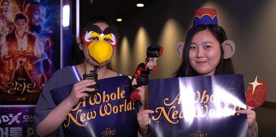 """지난달 19일 서울 CGV용산아이파크몰 '알라딘' 4DX 댄서롱 상영에서 극중 앵무새 이아고와 원숭이 아부 코스프레를 하고 참석한 관객들. """"내성적이어서 즐길 수 있을지 걱정했는데 목소리가 다 쉴 정도로 재밌게 봤다""""며 웃었다. [사진 CJ CGV]"""