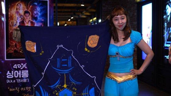 자스민 공주 분장을 하고 '알라딘' 4DX 댄서롱 상영을 찾은 관객, 그리고 양탄자. 극중 마법 양탄자를 코스프레한 것으로 실제 천 안에 사람이 들어가있다. [사진 CJ CGV]