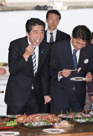 아베 신조 일본 총리가 2013년 10월19일 일본 후쿠시마현 근해에서 잡은 문어를 시식하고 있다. 일본은 2020년 도쿄 올림픽에서 후쿠시마산 농수산물을 적극 활용할 것이라고 밝혔다. AFP 제공