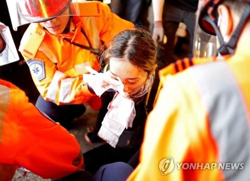 경찰 진압장비에 부상한 홍콩 시위 참가 여성 (홍콩 로이터=연합뉴스) 지난 11일 홍콩 침사추이 지역에서 벌어진 '범죄인 인도 법안'(송환법) 반대 시위에서 한 여성 시위 참가자가 경찰이 쏜 고무탄으로 추정되는 물체에 오른쪽 눈을 맞아 부상한 직후 구조대의 응급처치를 받고 있다. leekm@yna.co.kr