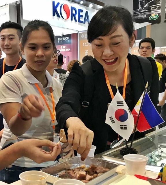 '필리핀식품박람회(WOFEX 2019)'를 찾은 현지인들이 대표적인 야식인 소주+족발 세트를 맛보고 있다. [aT 제공]