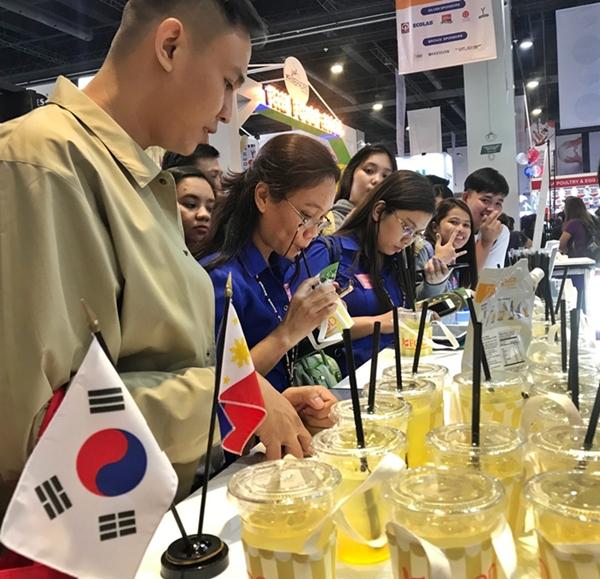 '필리핀식품박람회(WOFEX 2019)' 한국관을 찾은 현지인 등 방문객들이 시원한 여름 음료로 각광받고 있는 유자에이드를 시식하고 있다. [aT 제공]
