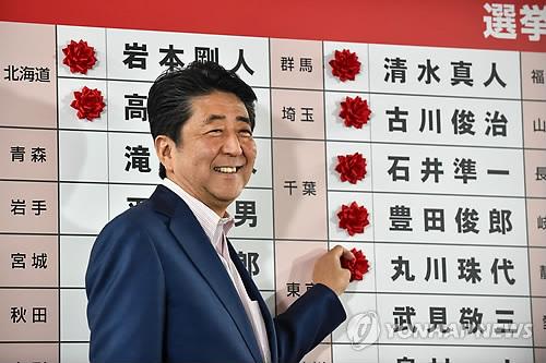 지난달 21일 아베 신조 일본 총리가 도쿄 자민당 당사에서 참의원 선거 당선자들 이름 옆에 장미꽃 조화를 붙이는 모습 [AFP=연합뉴스 자료사진]