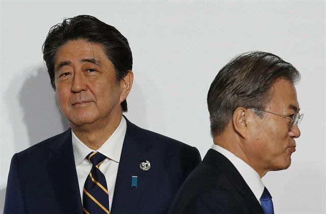 문재인 대통령과 아베 신조 일본 총리가 6월 28일 오사카에서 열린 주요 20개국 정상회의 공식 환영행사에서 8초간 악수만 나눈 뒤 지나치고 있다. 오사카=AP 연합뉴스