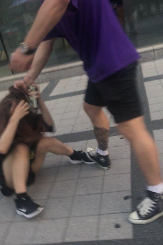 일본인 여성이 한국 남성으로부터 폭행을 당했다는 트위터에 첨부된 사진. 남성이 바닥에 쓰러진 여성의 머리채를 잡고 있다. [사진 트위터]