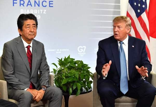 """도널드 트럼프 미국 대통령(오른쪽)과 아베 신조 일본 총리가 지난달 25일 오후 주요 7개국(G7) 정상회의 장소인 프랑스 비아리츠에서 정상회담을 하고 있다. 당시 트럼프 대통령은 """"중국이 사지 않은 옥수수를 일본이 대신 사기로 했다""""고 자랑했다. 비아리츠/AFP 연합뉴스"""