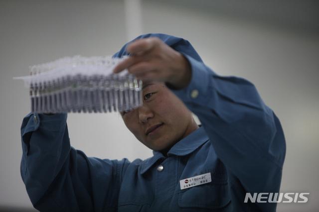 지난 2009년 9월 3일 중국 베이징에 있는 제약회사 시노백 바이오테크에서 한 직원이 생산중인 H1N1 독감 백신 제품을 살펴보고 있다.
