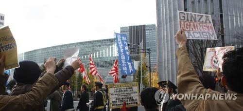 """2018년 12월 9일 일본 우익세력이 도쿄(東京) 도심에서 혐한(嫌韓) 시위를 연 가운데 이에 반대하는 시민들이 시위대를 따라다니며 """"노(No) 헤이트(hate)"""" 등이 적힌 종이 등을 들고 맞불 시위를 하고 있다. [연합뉴스 자료사진]"""